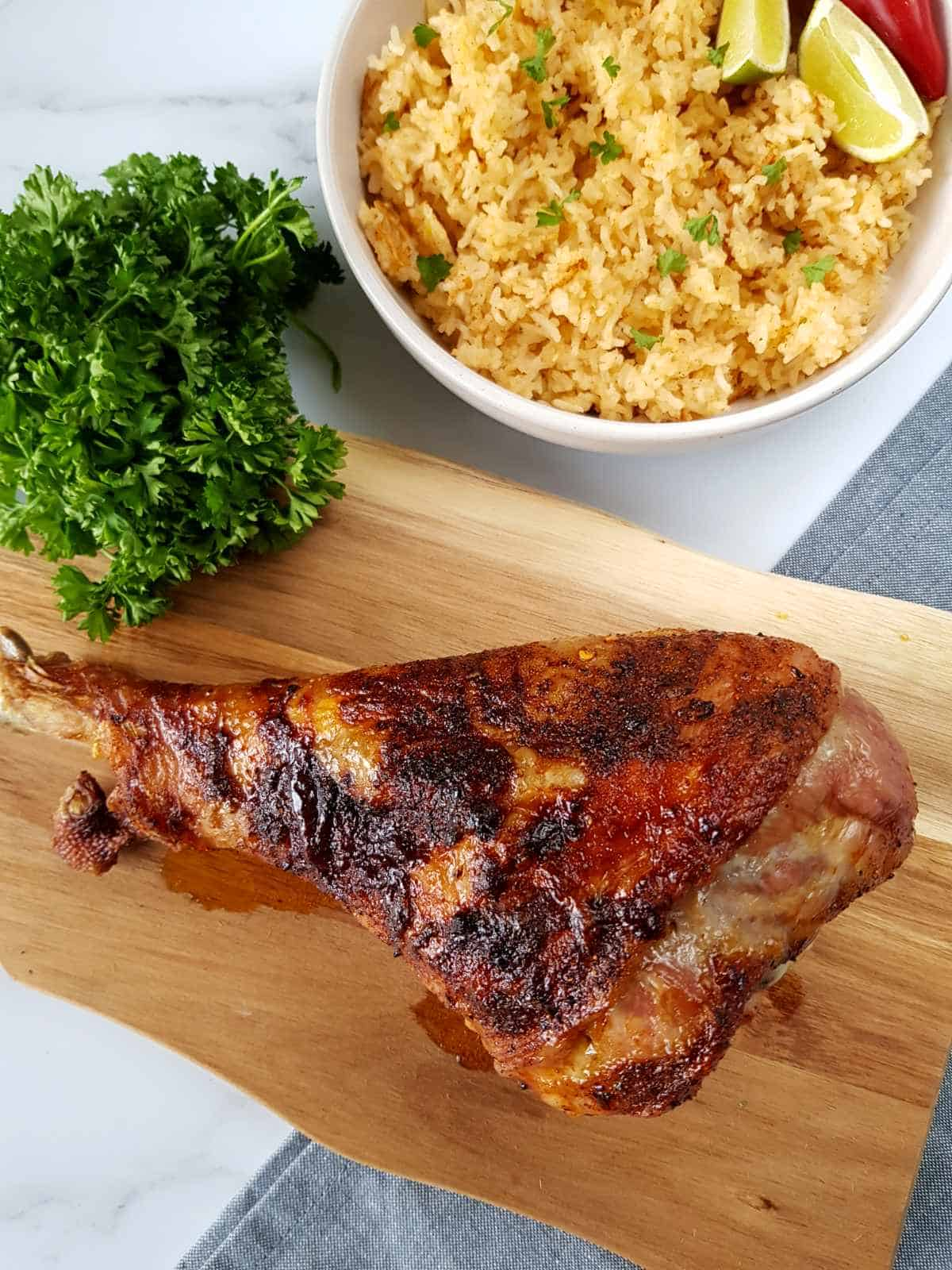 Moroccan roasted turkey drumstick on a wooden board with fresh herbs and rice on the side.
