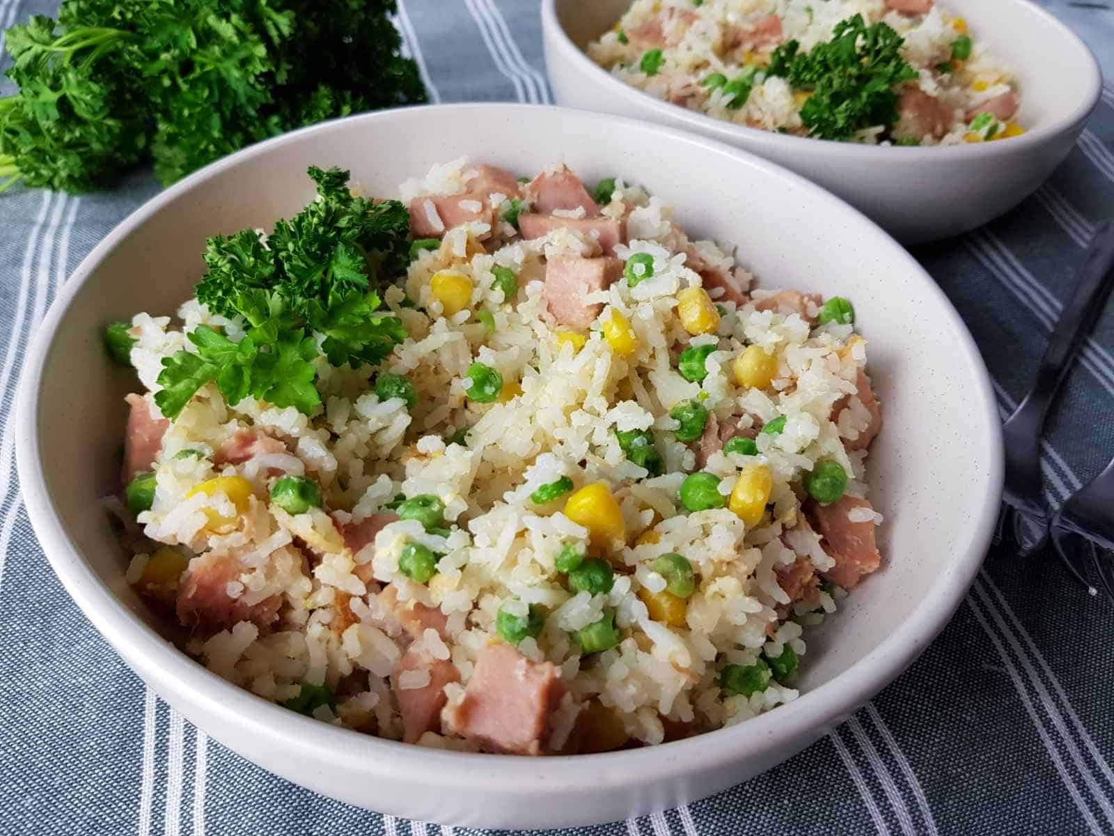 Gammon fried rice in white bowls on a tablecloth with fresh herbs.