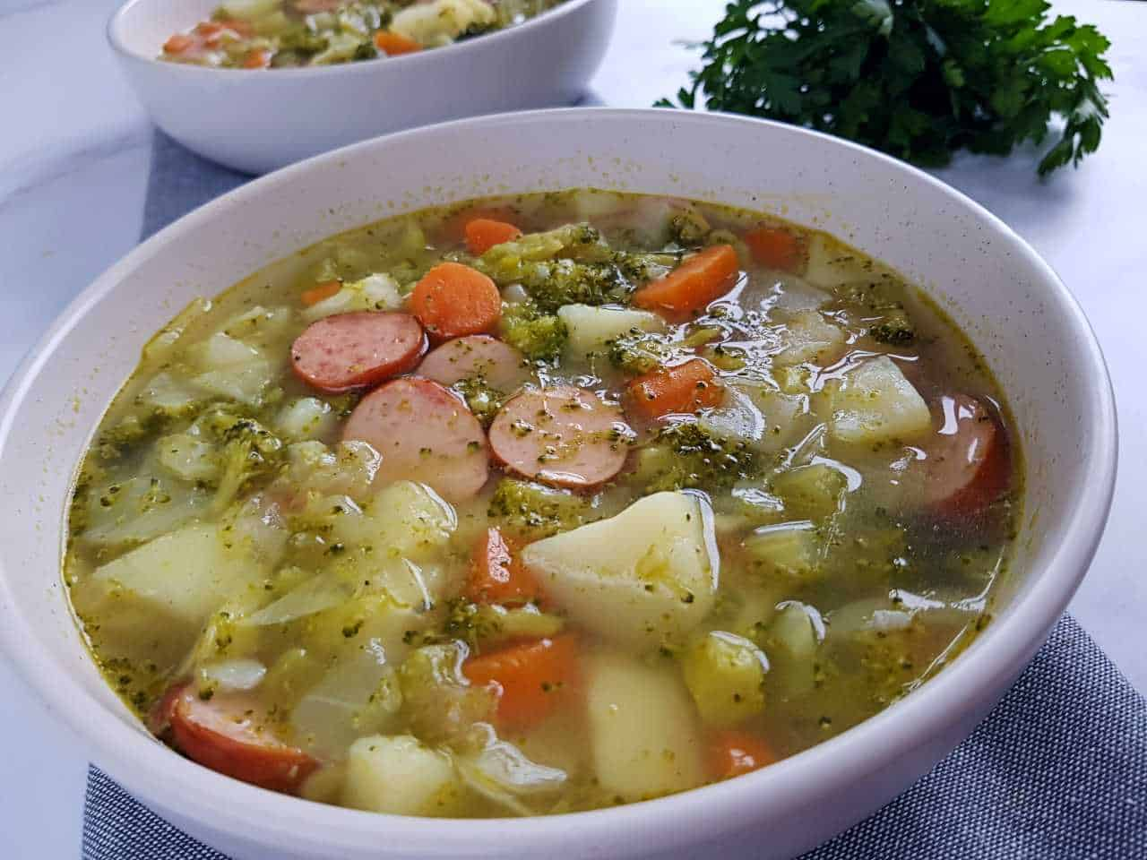 Sausage and vegetable soup in white bowls.