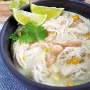 White chicken chili in gray bowls with lime and herbs on top