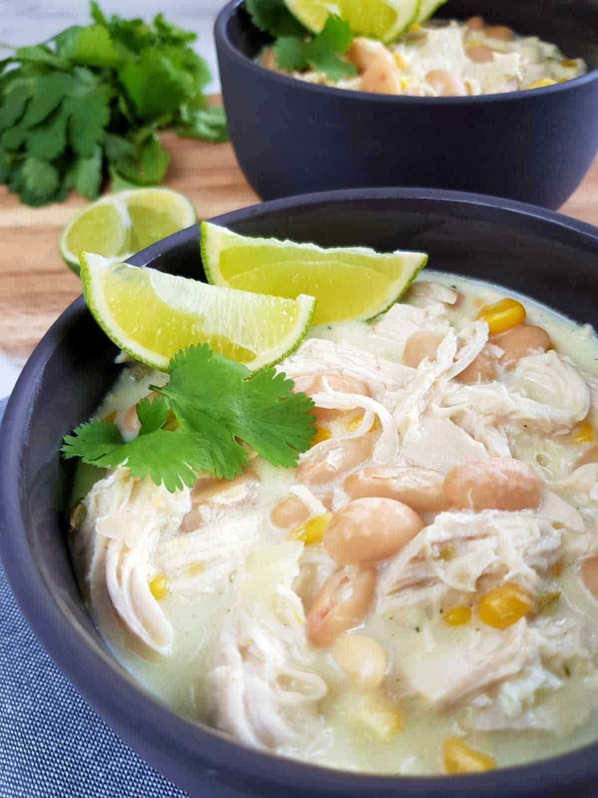 White chicken chili in gray bowls with lime and herbs on top,
