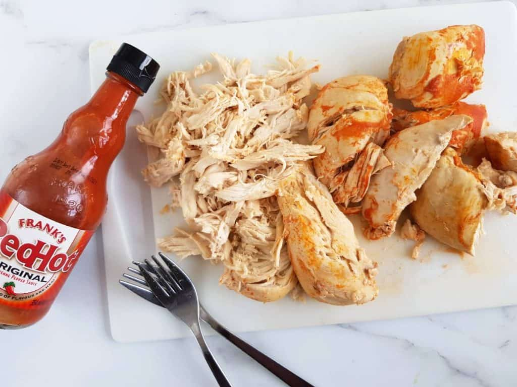 Buffalo chicken on a chopping board with two forks and buffalo sauce on the side.