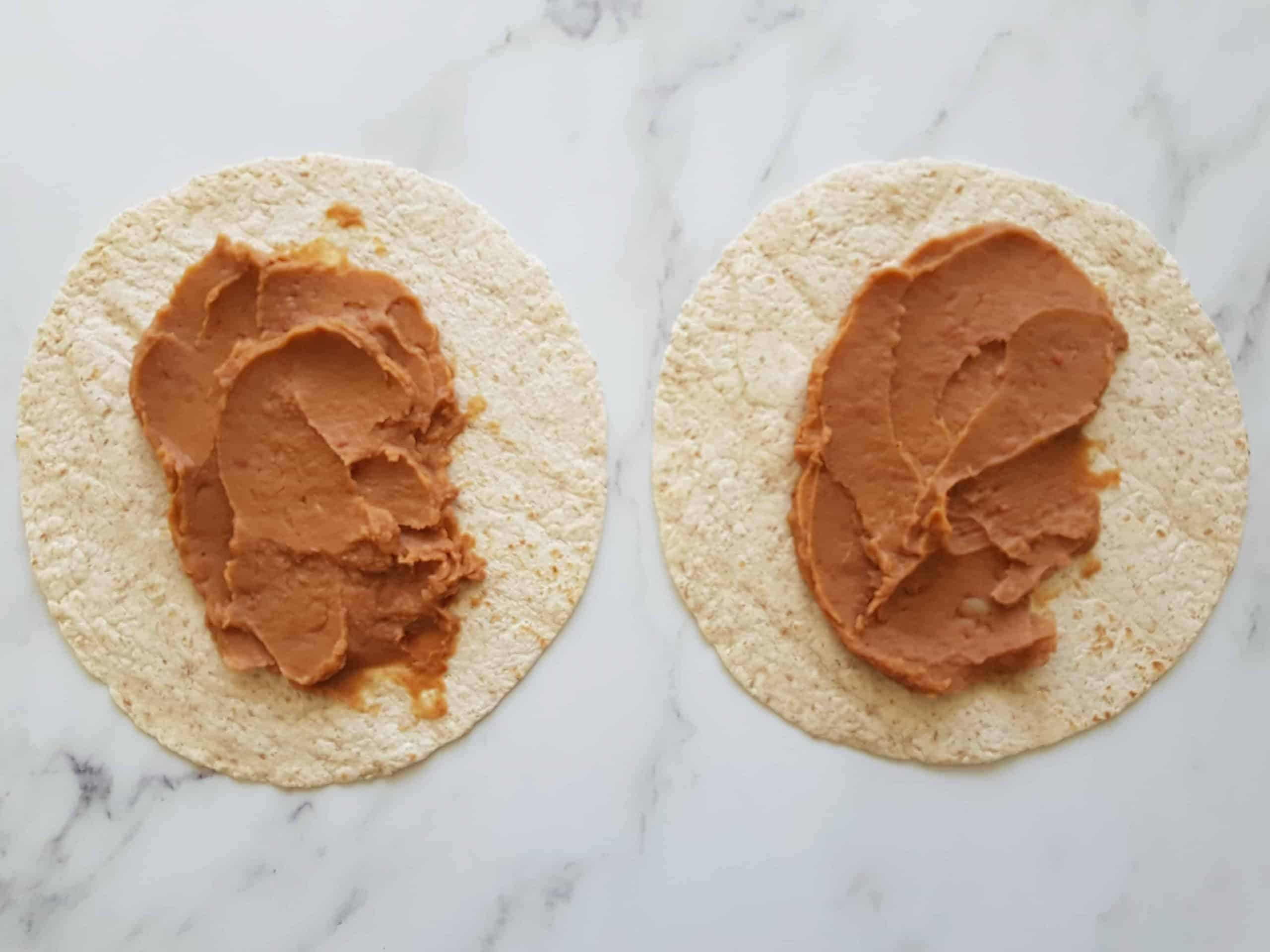 Tortilla wraps with refried beans on top.