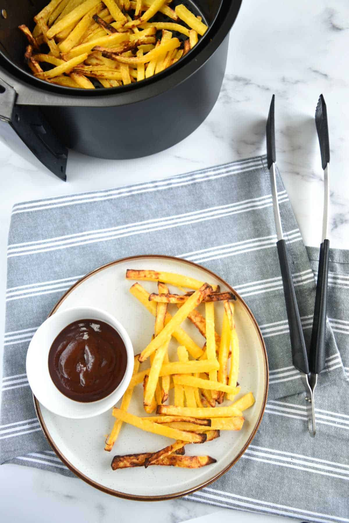 Rutabaga fries on a plate with BBQ sauce, with tongs and an air fryer next to it.