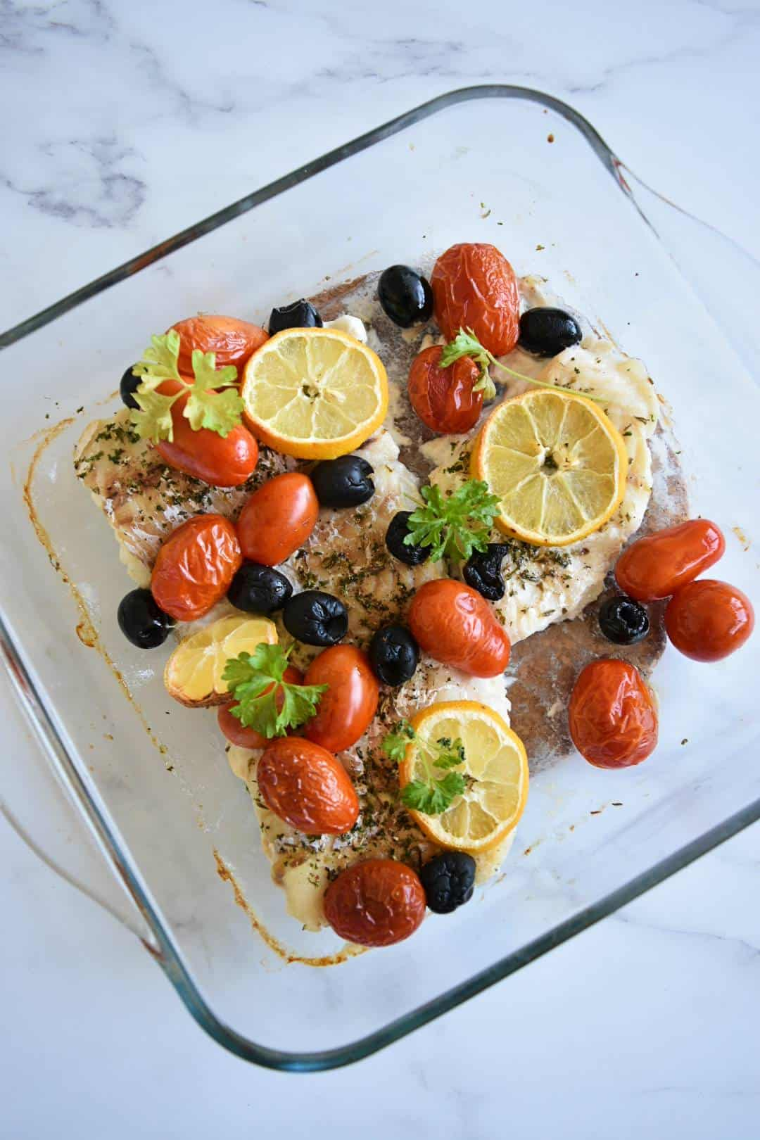 Tomatoes, olives and cod bake with fresh herbs and lemon sliced on top.