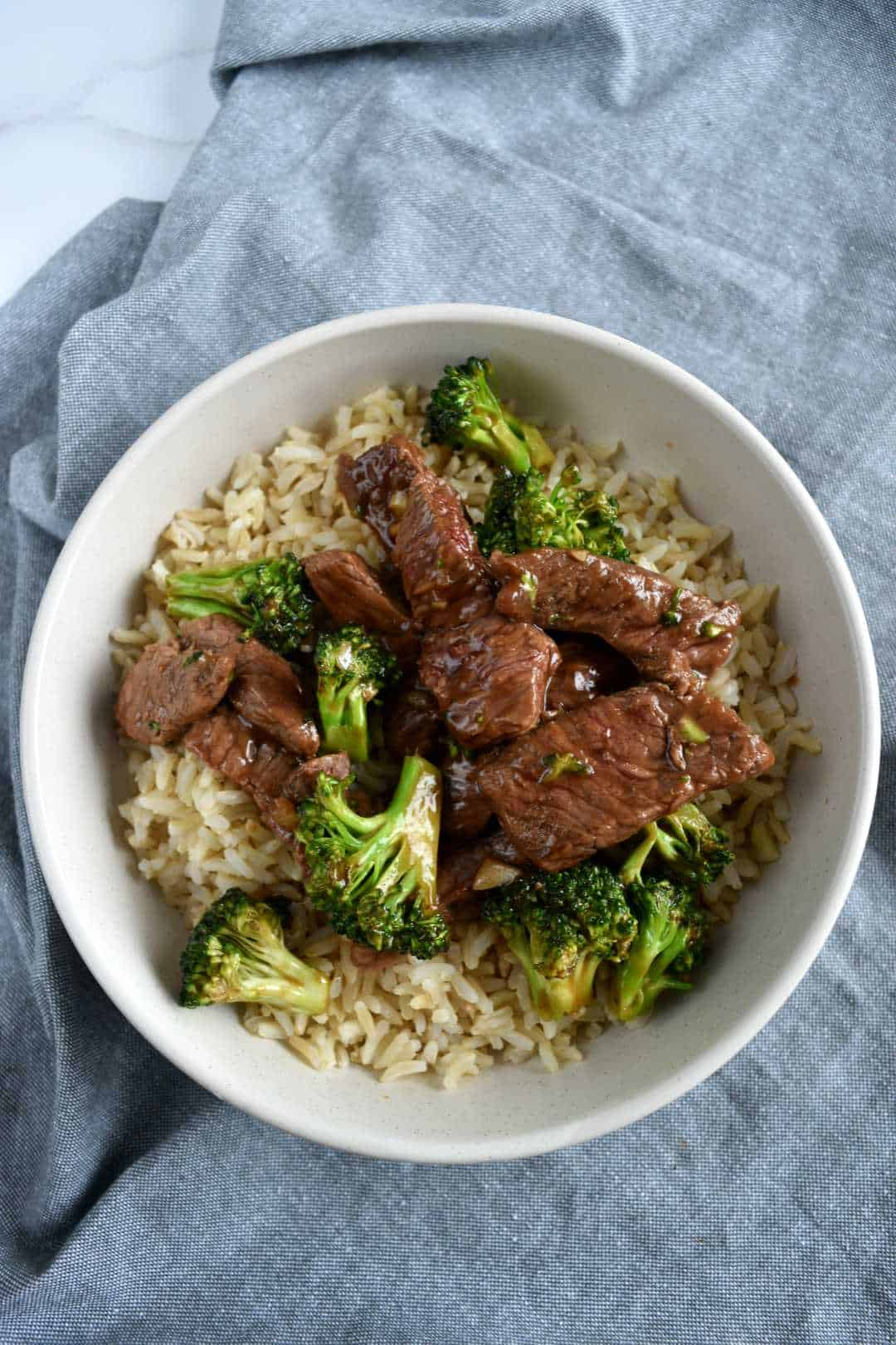 Broccoli and beef stir fry in a white bowl with rice.