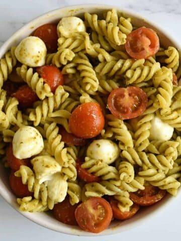 Caprese pasta pesto salad in a bowl.