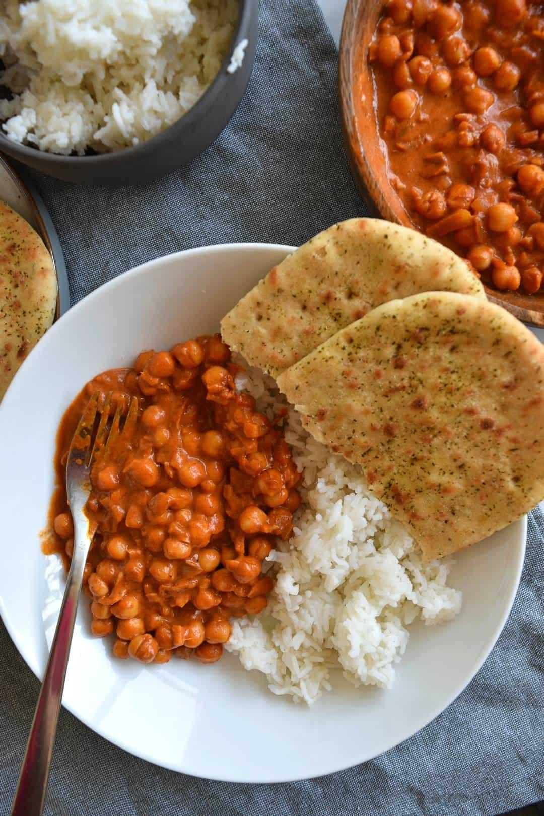 Chana masala, rice and naan bread in a bowl.