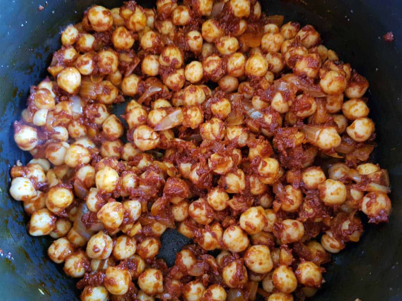 Chickpeas in a pot with tomato paste and spices.