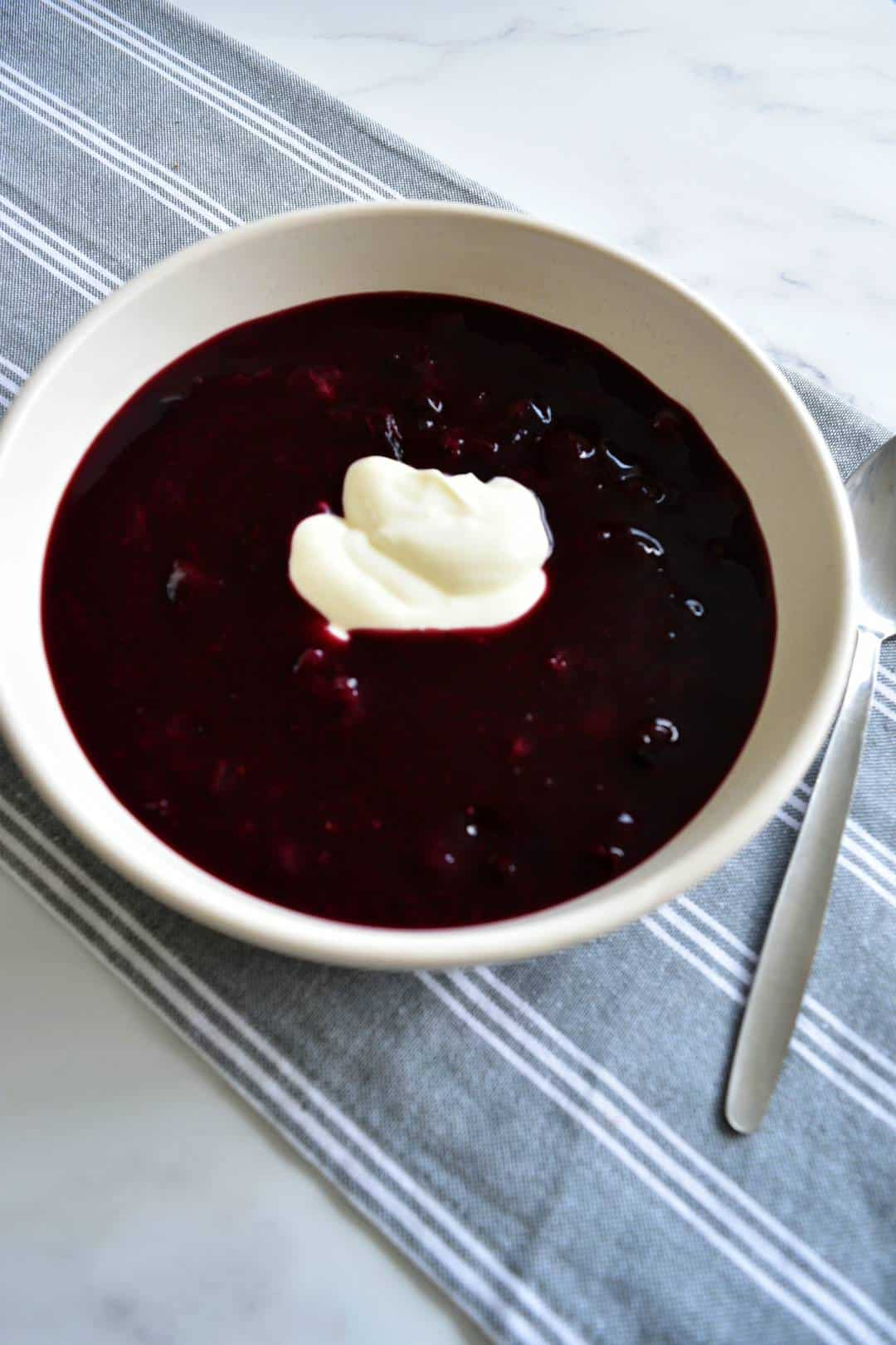 Blueberry soup topped with yogurt in a white bowl with a spoon on the side.