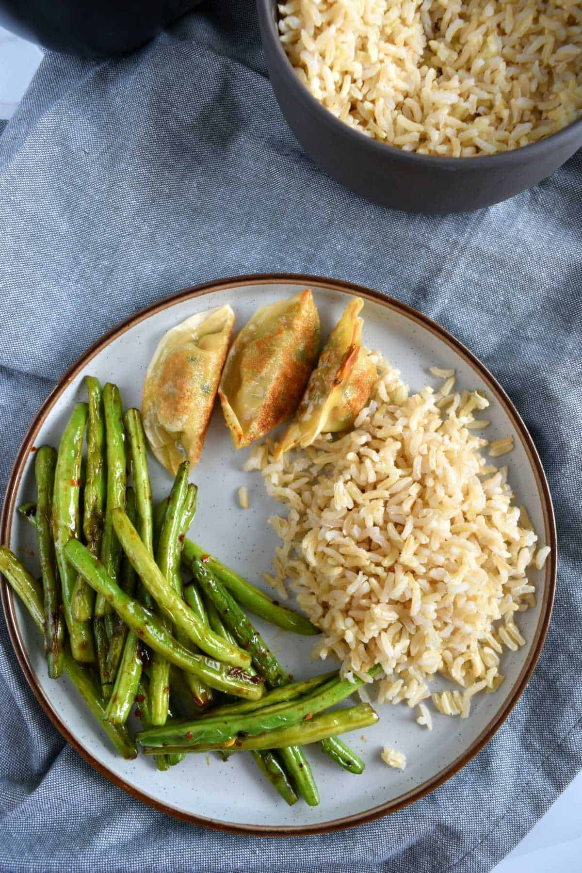 Green beans, potstickers and rice on a plate with a bowl of rice in the background.