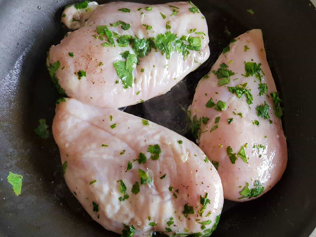 Chicken breast fillets with cilantro in a frying pan.