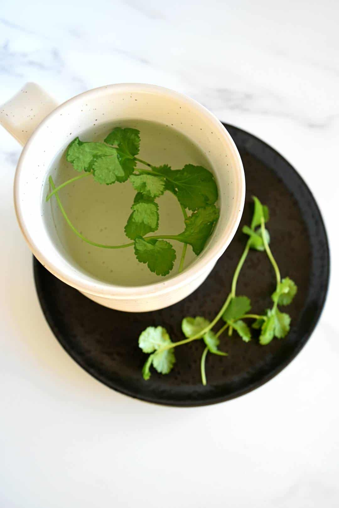 Cilantro tea steeping in a cup.