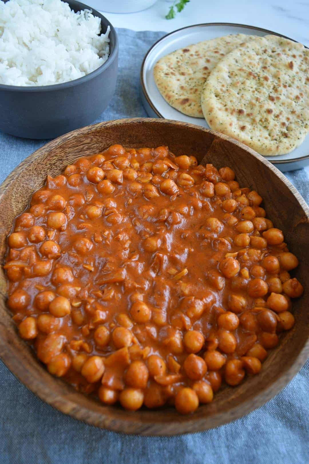 Chana masala in a wooden bowl with rice in the background.