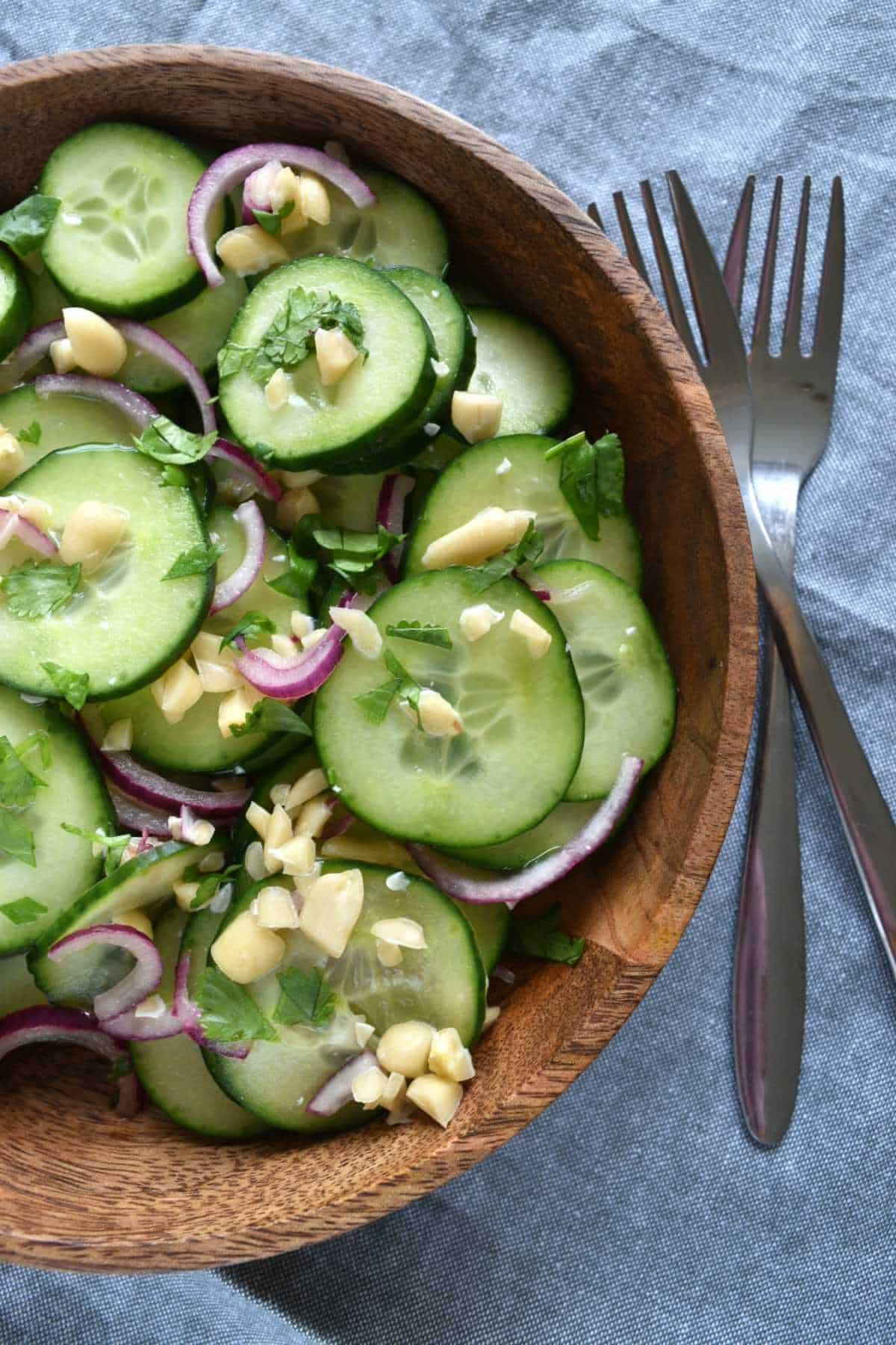 Cucumber salad in a wooden bowl with two forks on the side.