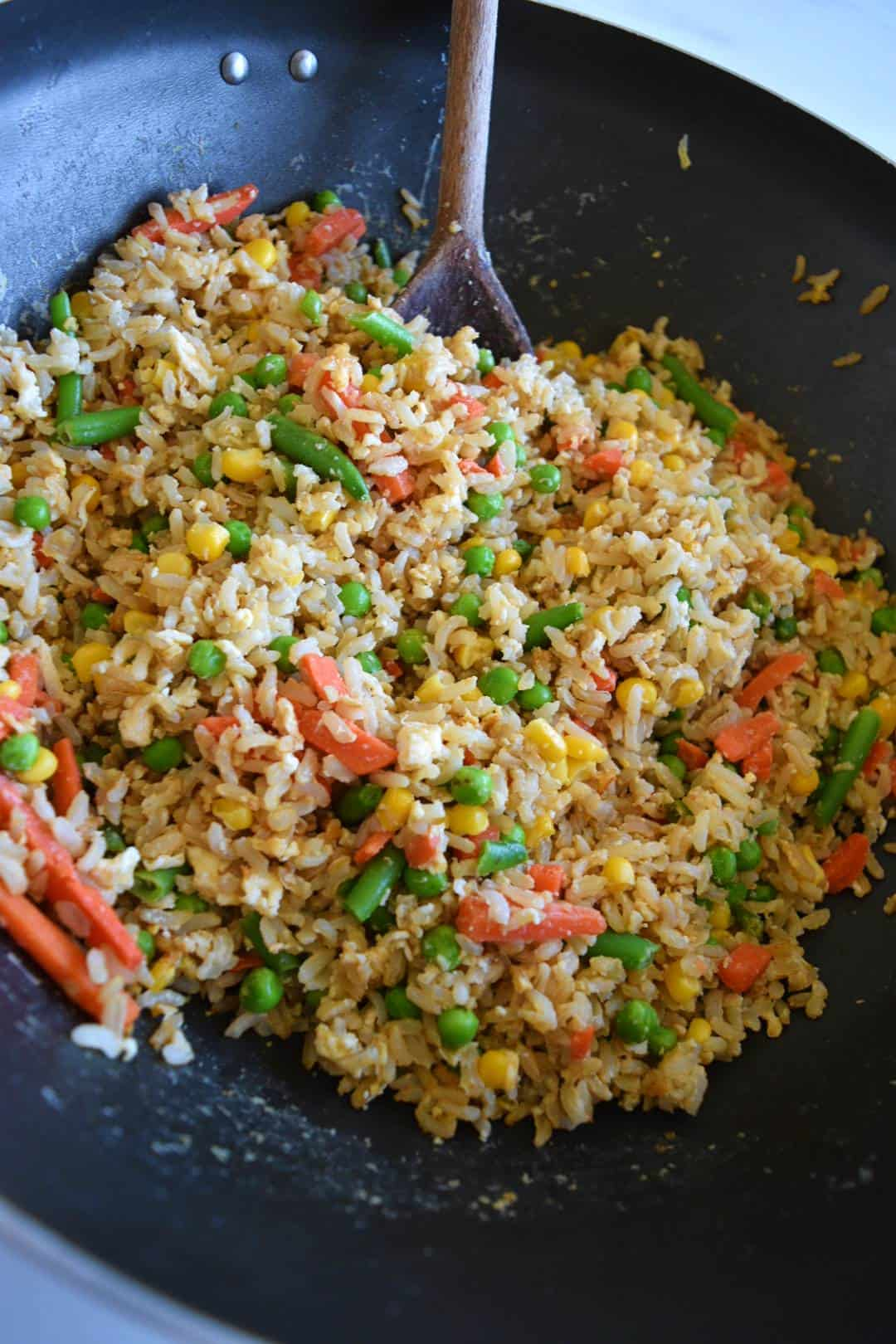 Egg fried brown rice in a wok.