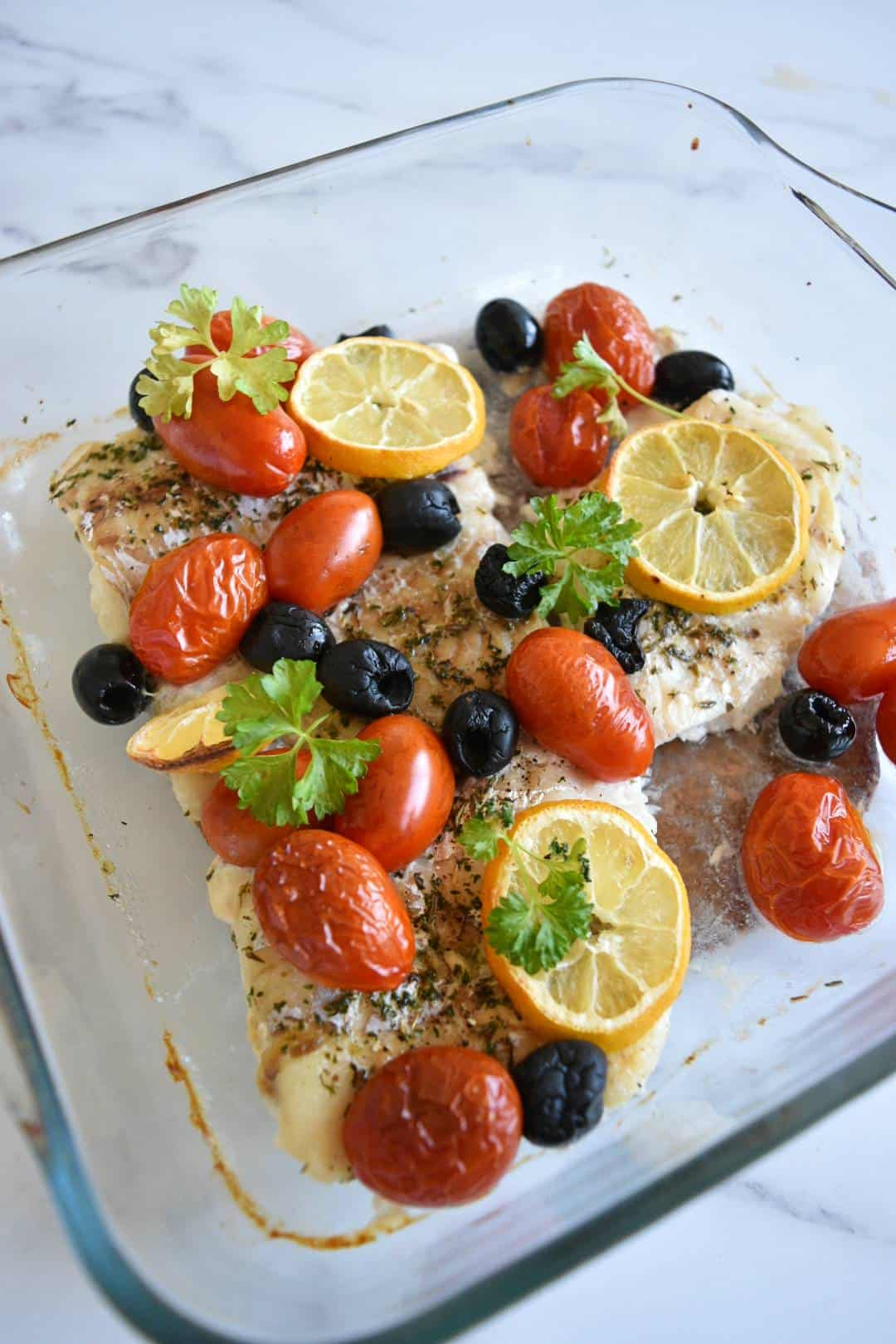Mediterranean baked cod with olives and tomatoes in an oven proof dish.