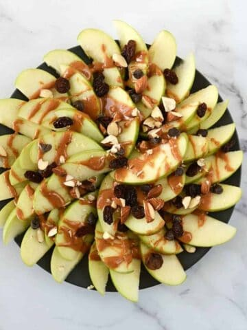 Peanut butter apple nachos on a plate on a marble table.