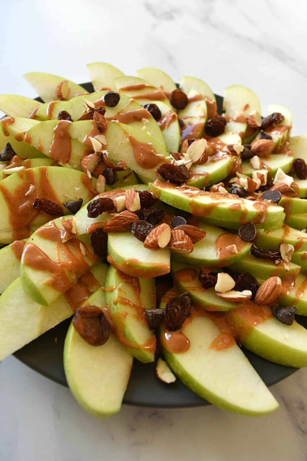 Peanut butter apple nachos topped with raisins, almonds and chocolate chips.