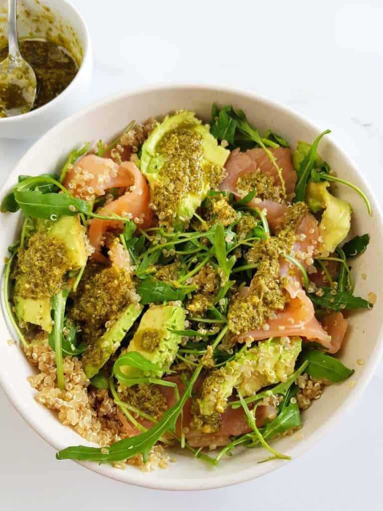 Smoked salmon and quinoa salad with avocado and arugula in a bowl.