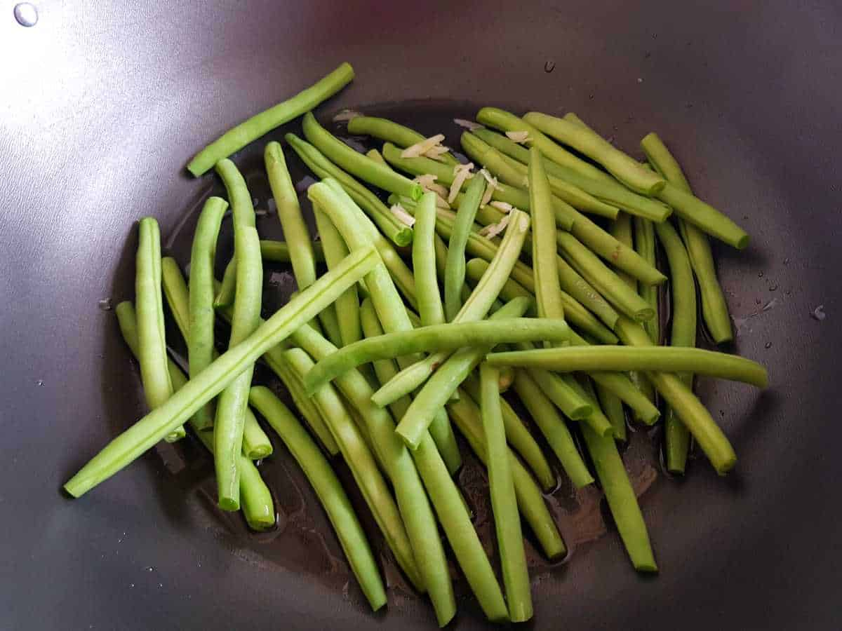 Green beans cooking in a wok.