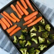 Roasted carrots and broccoli on a sheet pan.