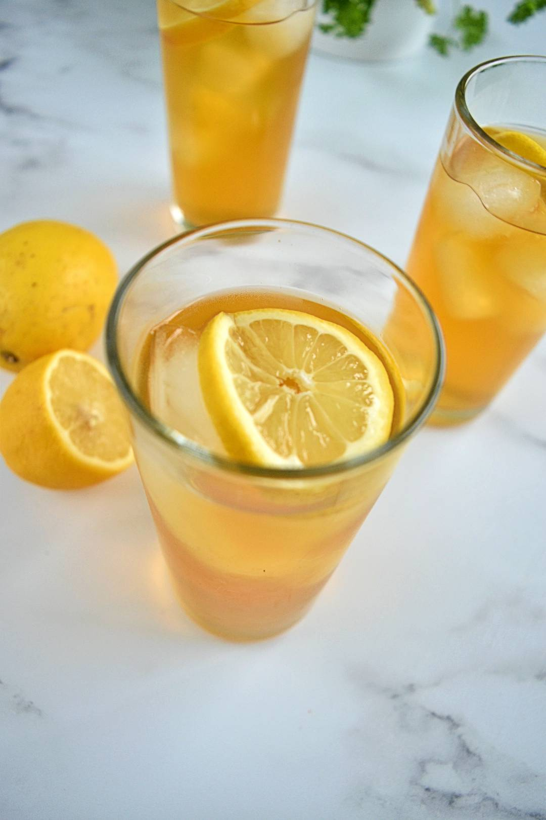 Rooibos iced tea in glasses with ice cubes and lemon slices.