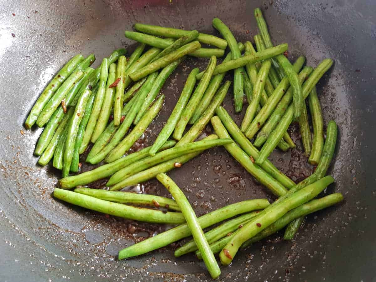 Green beans in a wok covered with stir fry sauce.