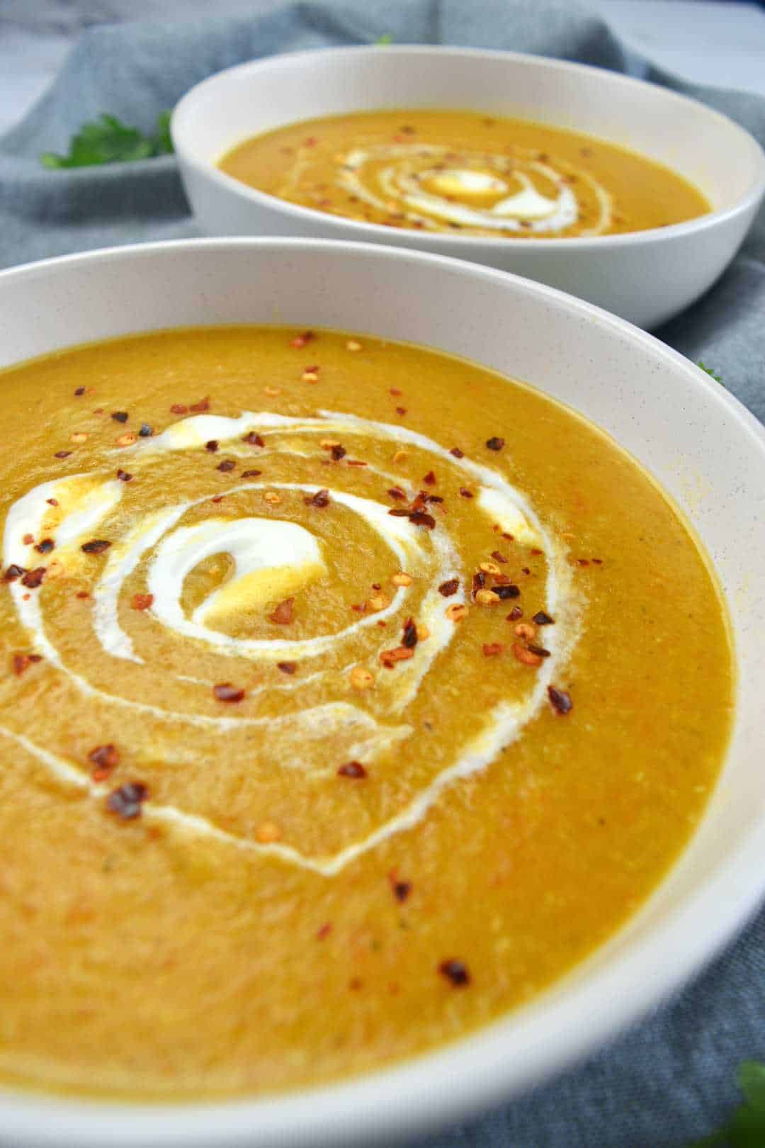Red lentil soup in white bowls with chili flakes on top.