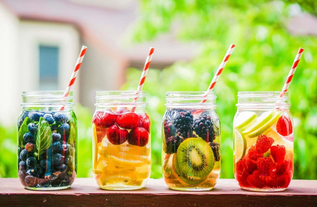 Mason jars with water, fresh fruit and straws.
