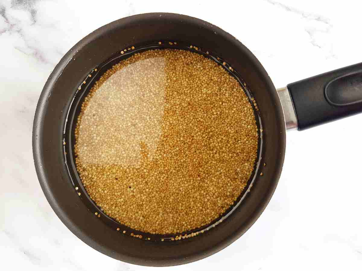 Quinoa in a black saucepan on a marble table.