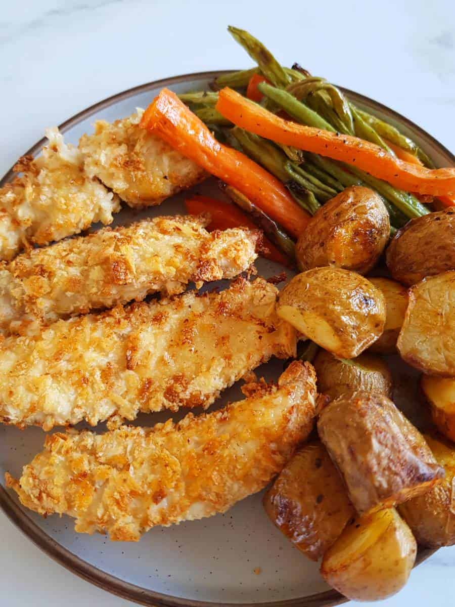 Breaded chicken on a plate with roasted vegetables.