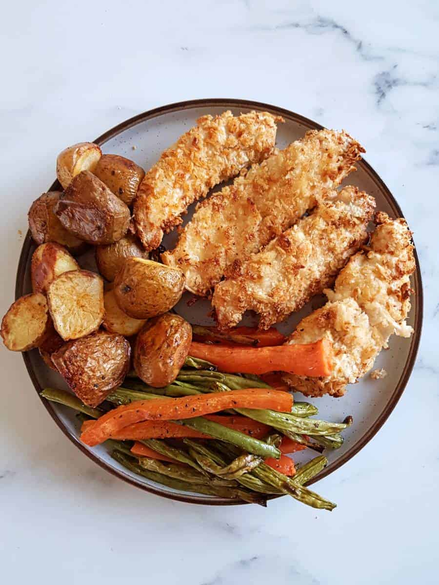 Air fryer breaded chicken on a plate with roasted carrots, green beans and potatoes.