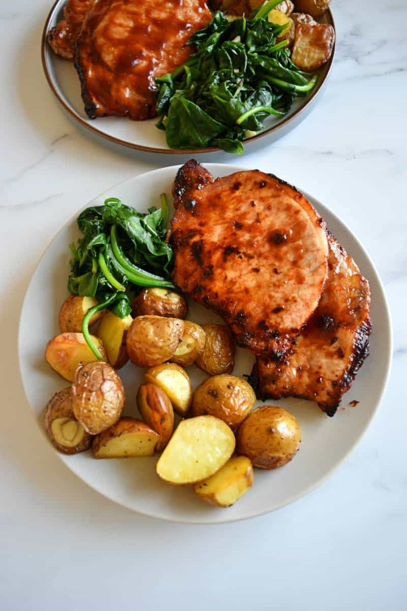 Air fryer pork chops on a plate with spinach and potatoes.