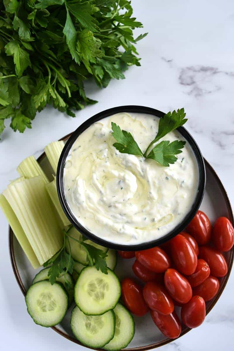 Authentic Tzatziki sauce on a plate with veggies on the side.