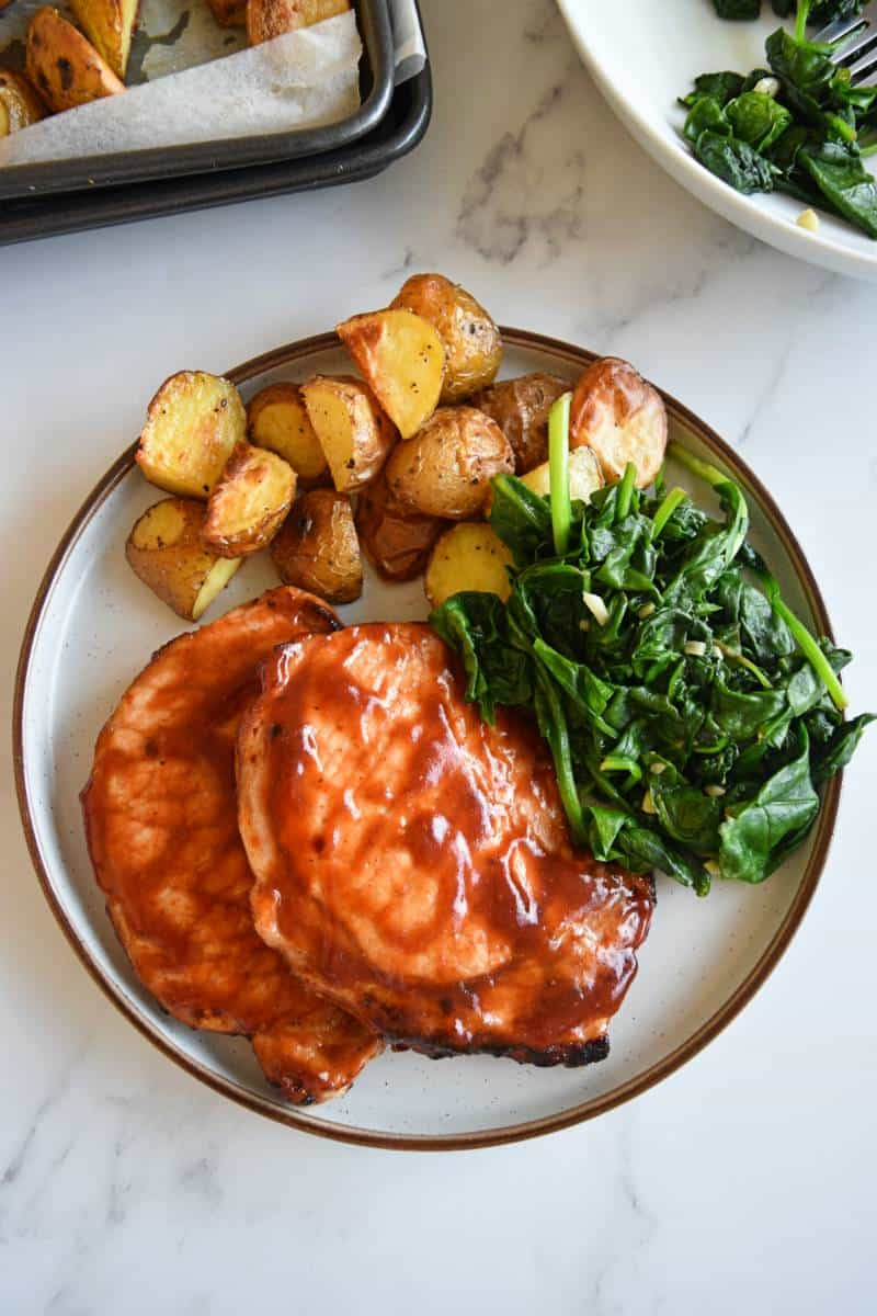 BBQ pork chops with greens and potatoes.