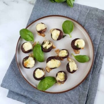Basil and mozzarella stuffed mushrooms on a plate with basil leaves.