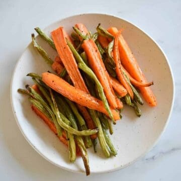 Carrots and green beans on a white plate on a marble table.