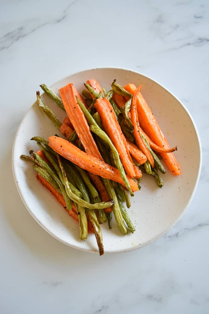 Roasted carrots and green beans on a plate.