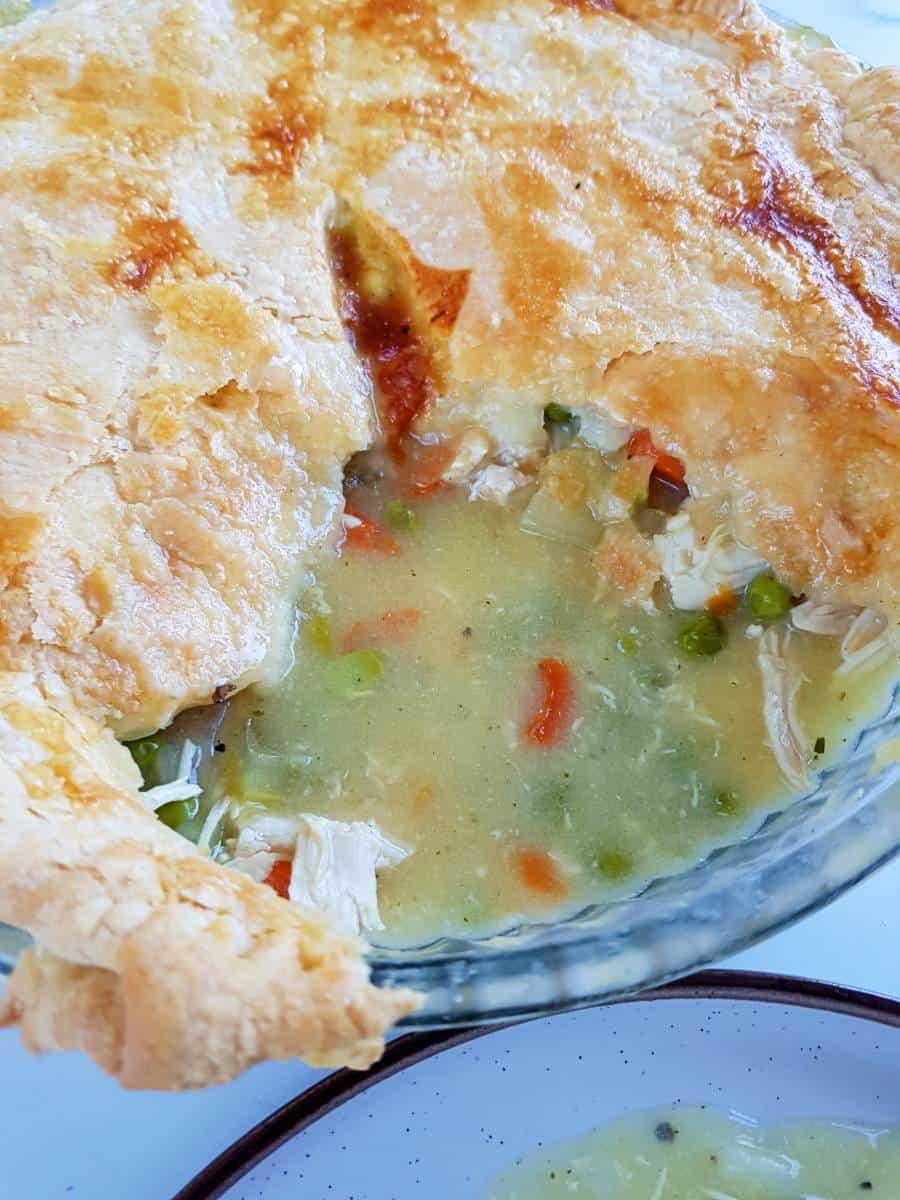 Chicken pot pie with almond milk and a slice cut out.