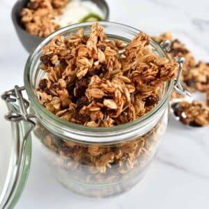 Granola with cinnamon and raisins in a mason jar.