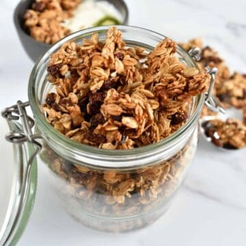 Granola with cinnamon and raisins in a mason jar.