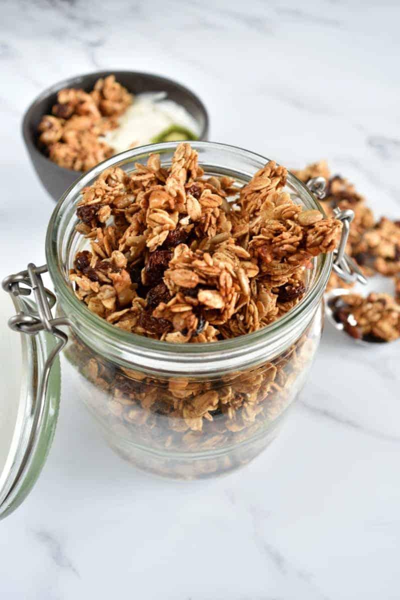 Cinnamon raisin granola in a jar on a marble table.
