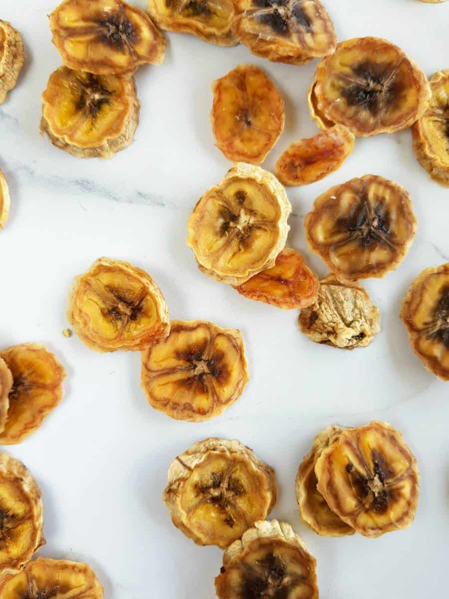 Dried banana slices on a marble table.
