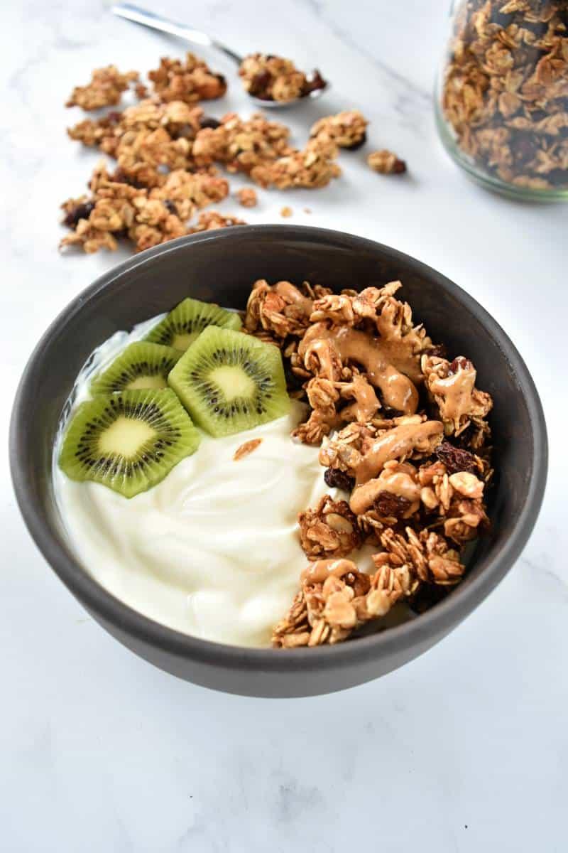A bowl of yogurt, granola and sliced kiwi.