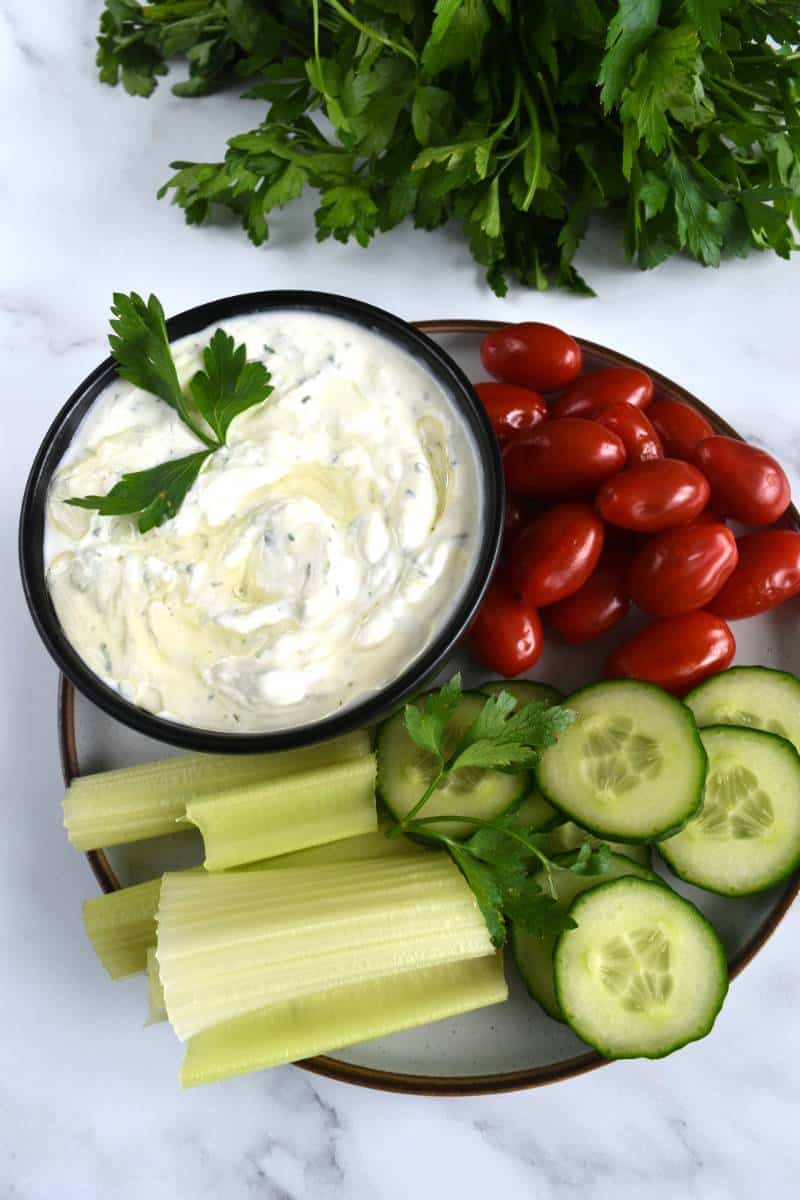 Greek tzatziki in a bowl with raw vegetables on the side.