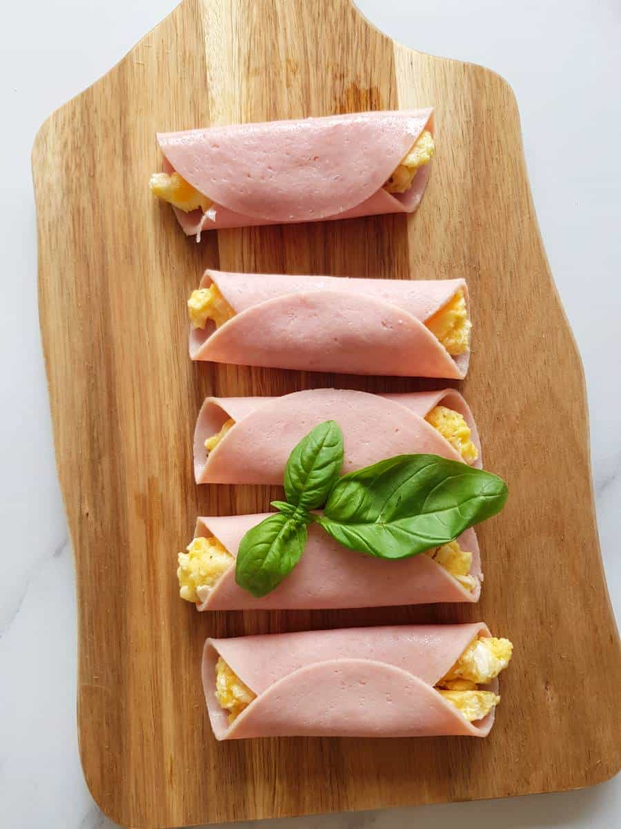 Ham egg and cheese rollups on a wooden board.