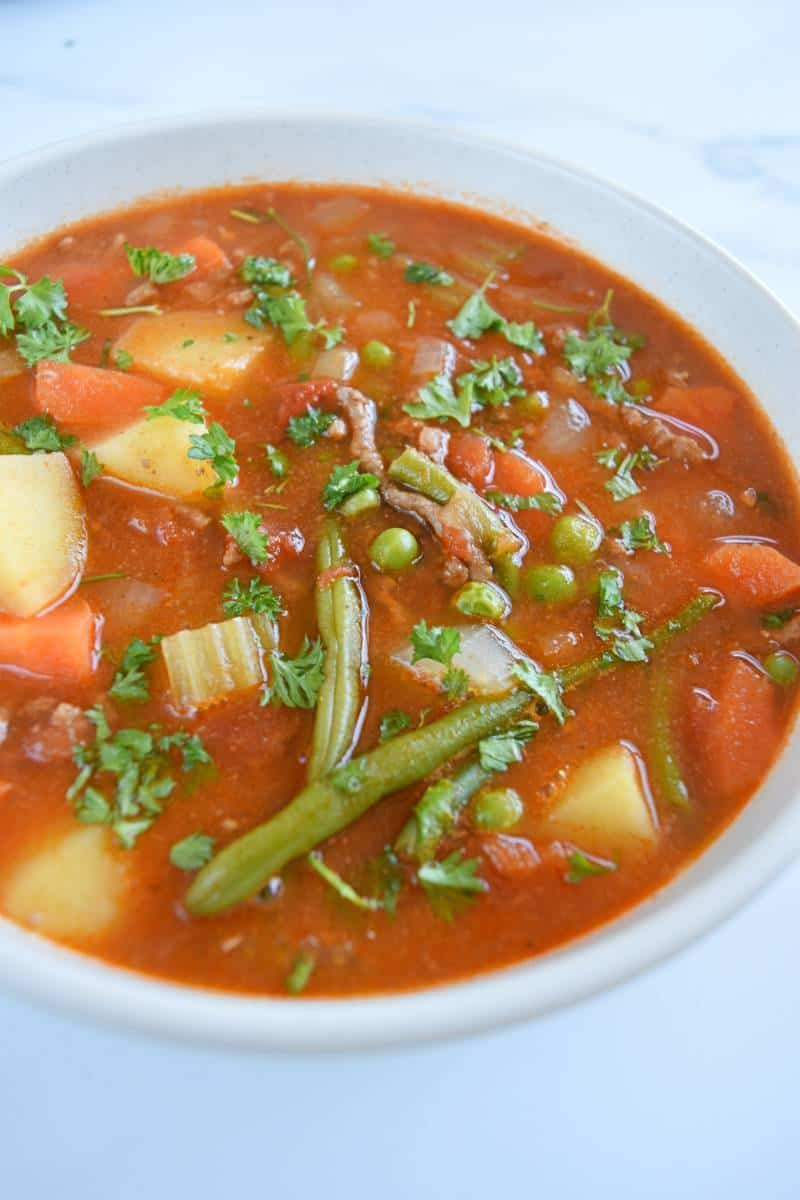 Hamburger vegetable soup in a white bowl.