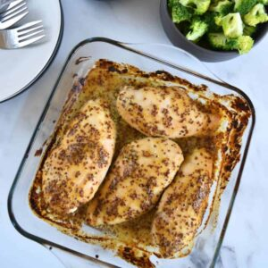 Honey mustard chicken in a casserole dish. on a marble table.