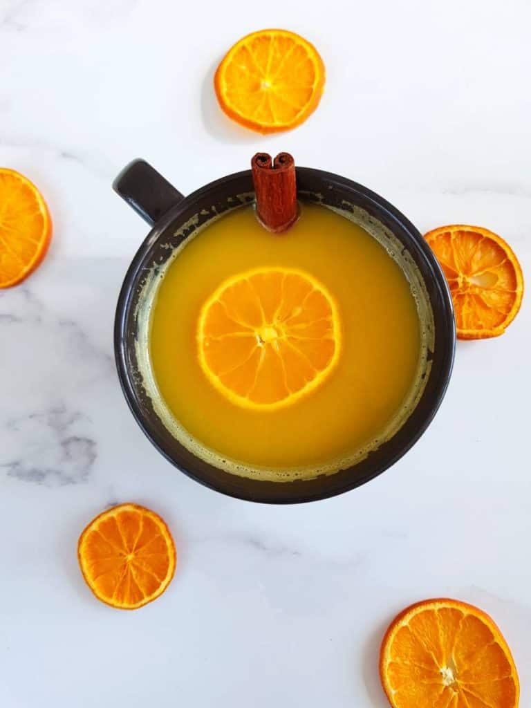 Hot orange juice in a cup surrounded by dried orange slices.